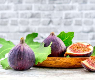 fig fruit on a wooden table with a brick background